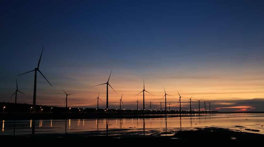 wind mills reflecting on a pond while the sunsets in the distance