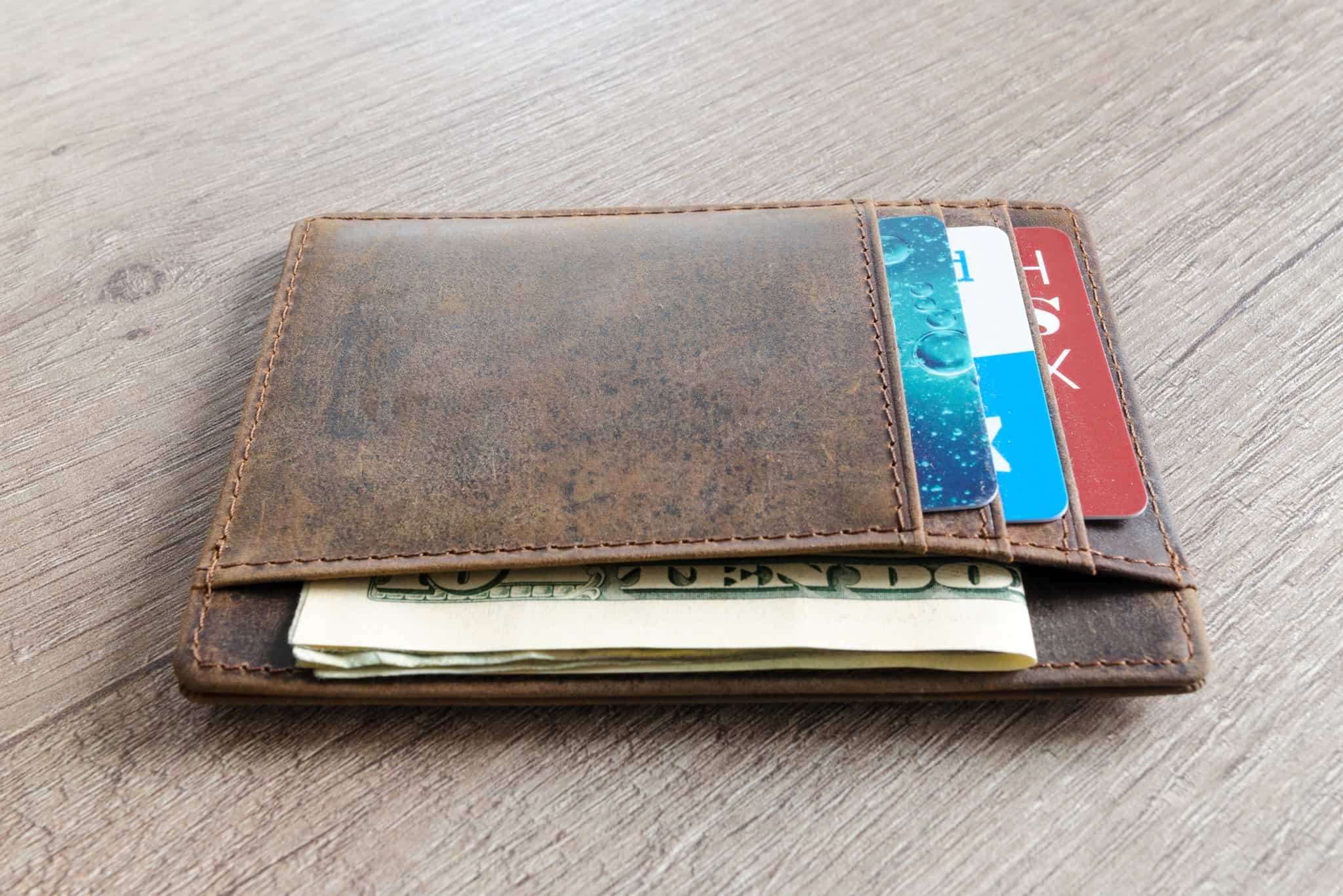 brown leather wallet on a desk with multiple credit cards and cash inside