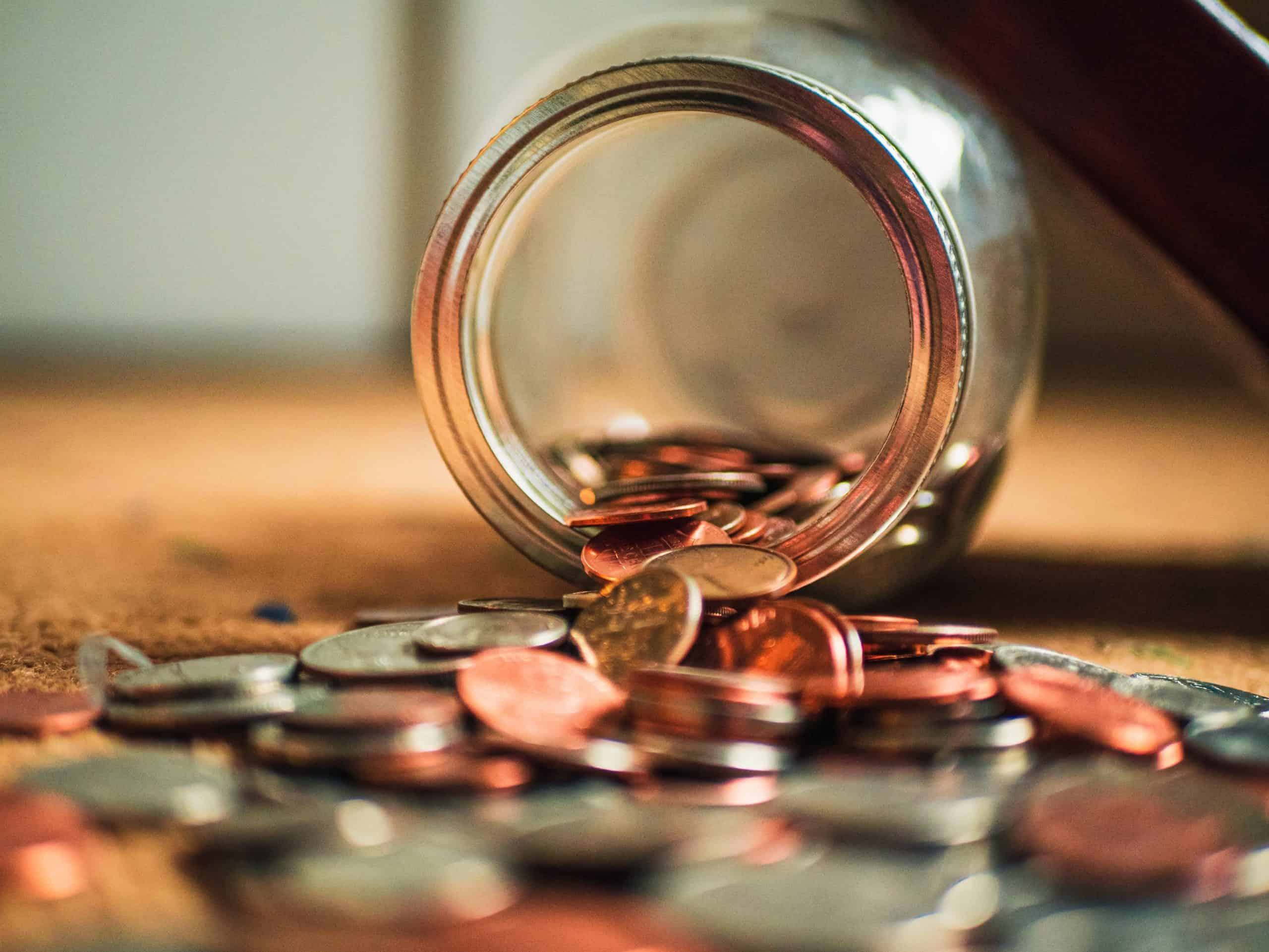 quarters dimes nickels and pennies pouring out of a mason jar on a hardwood floor