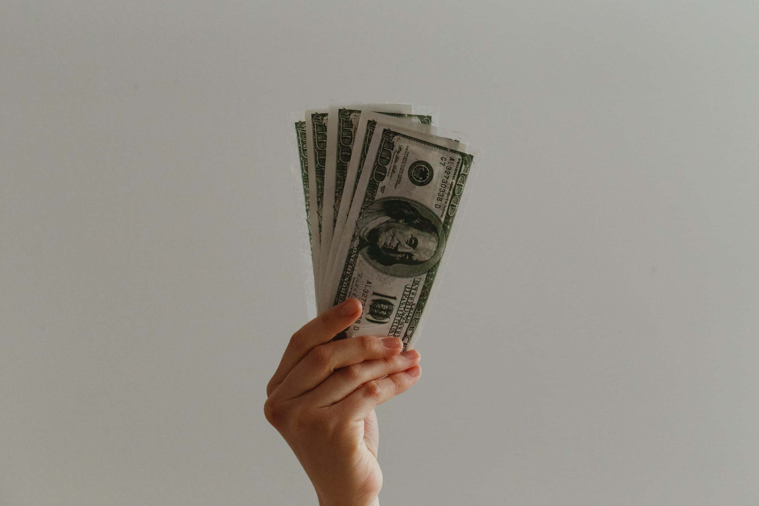 hand holding a stack of 100 dollar bills spread out in a fan in front of a white wall