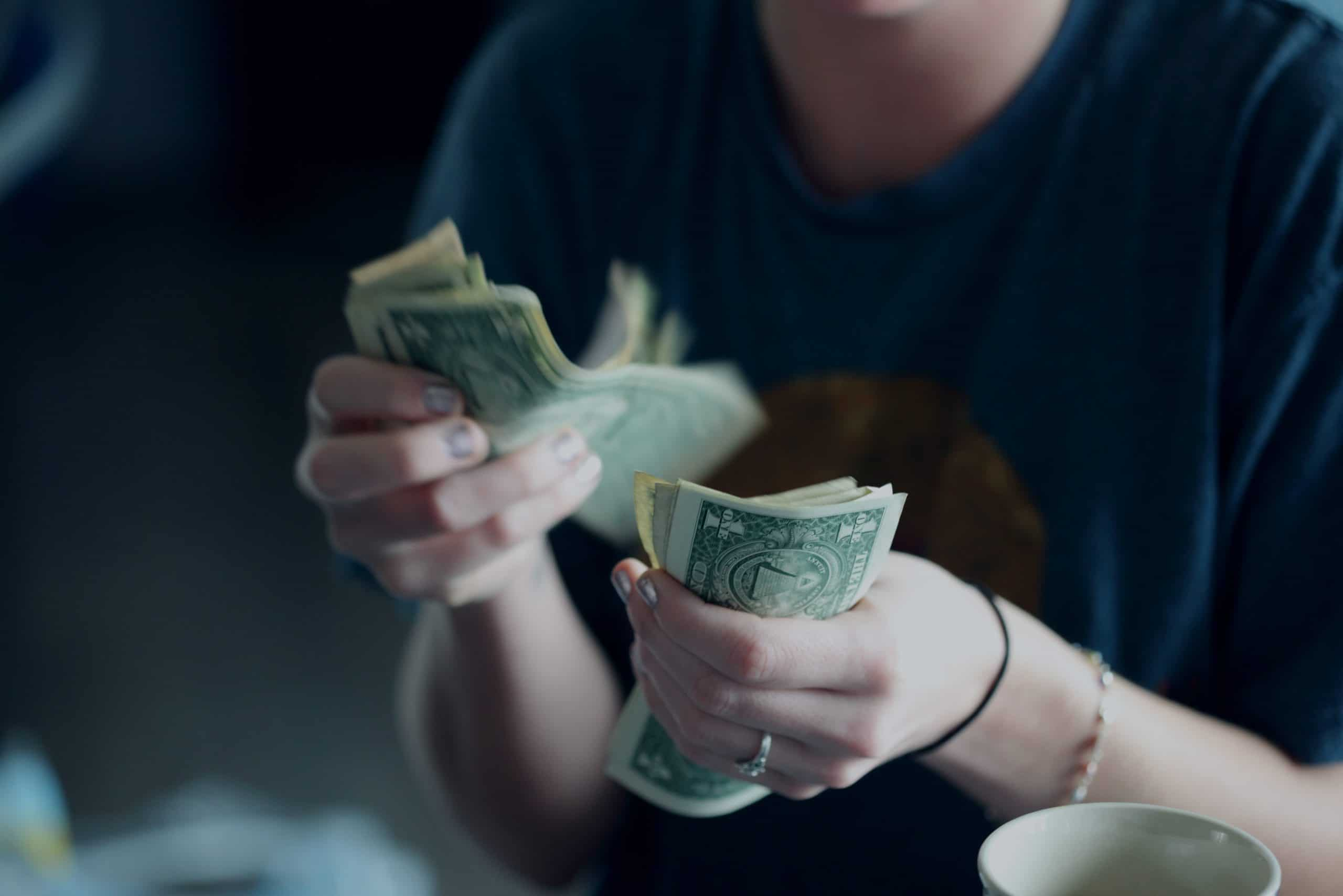 Women counting dollar bills over her morning coffee