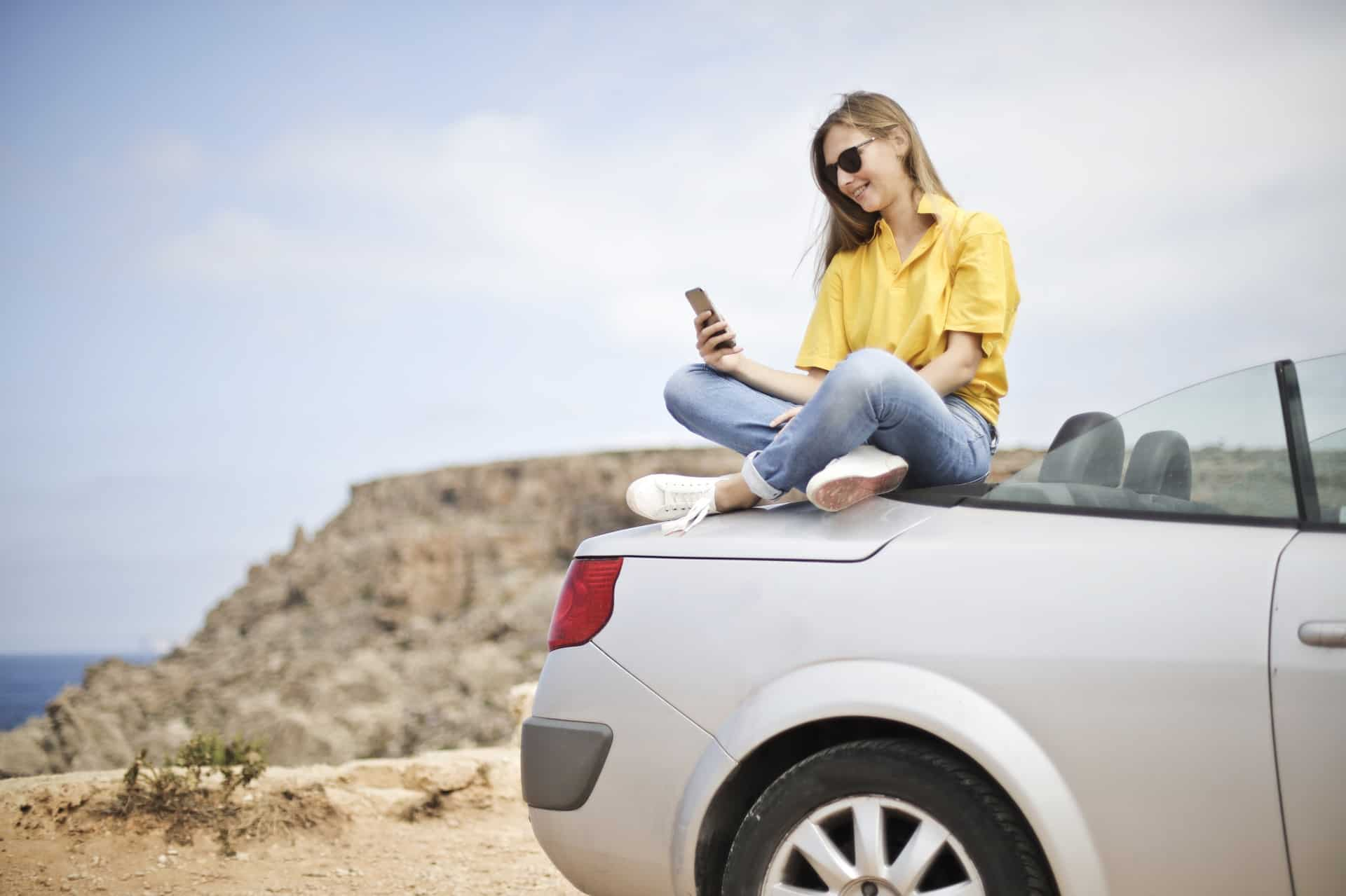 Young women wearing a yellow shirt sitting on the back of a grey convertible in the desert